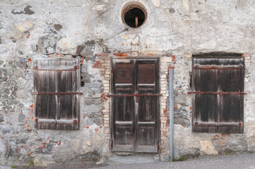 old weathered facade with a door and two Windows