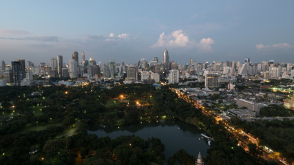 Evening Bangkok, Thailand. Panorama with modern highrise buildings, green park and transport traffic on long highway