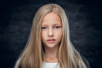 Studio portrait of blonde teenage girl on grey background.