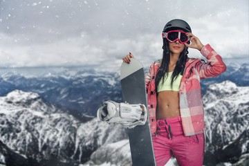 Sporty female holds snowboard in mountains.