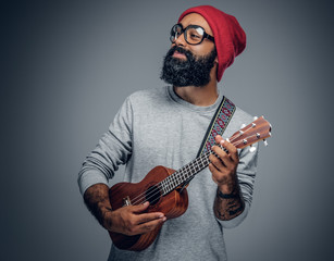Bearded hipster male in red hat playing on ukulele.
