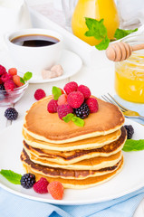 Stack of delicious american pancakes with berries on a white background