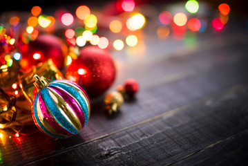 Christmas balls with Colorful Christmas lights on dark wooden ba