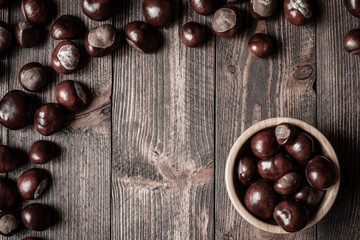 Pile of horse chestnuts on a bamboo bowl on wooden table - vintage