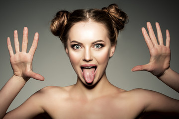 Emotional girl. Beautiful modern model shows tongue Positive wom