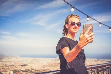 Summer day.Front view of smiling girl in sunglasses,black T-shirt,denim shorts and pink sneakers,standing and holding smartphone.In background view of Barcelona from Mount Tibidabo.Woman using gadget.