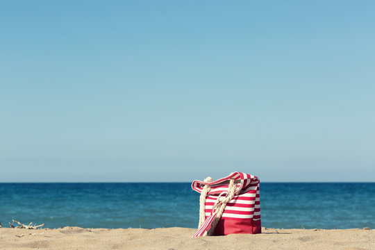 Beach bag on a sandy beach with a blue sea on a background