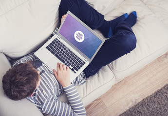 Young Person Lying on Couch with Laptop Mockup