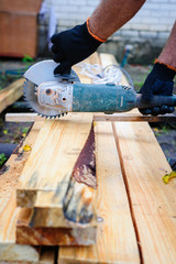 Men Use Hand Held Power Saw to Cut Planks of Wood for Home Const