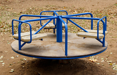 A blue carousel on a playground