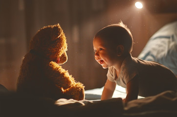 Happy baby laughing with teddy bear in bed