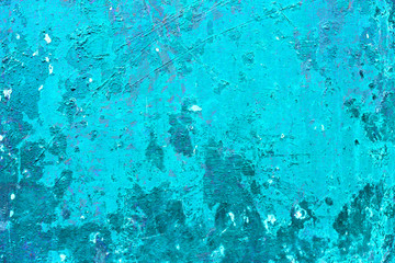 Cracked and peeling paint on the blue wall. Close-up view. Grunge old texture. Scratched and chipped surface.