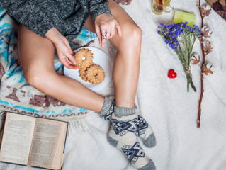 Long female feet in warm woolen socks with cup of tea and book