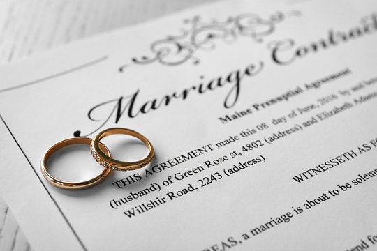 Golden wedding rings on marriage contract, closeup