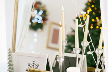 Candles and Christmas decor against mirror, close up view