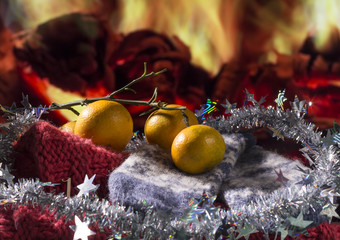 Christmas theme with tangerines, gloves and decorations on fireplace background