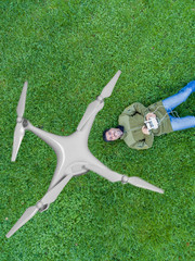 Luftbild Drohnenflug - Liegender Mann steuert Drohne mit Fernsteuerung