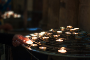 Woman lights candles church