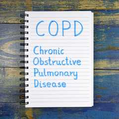 COPD- Chronic Obstructive Pulmonary Disease acronym written in notebook on wooden background