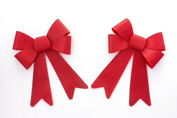 Two red holiday bows angled toward one another
