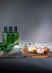 still life. bottle, onion, garlic, spinach, Hand mill, pepper on a blue tablecloth. space for text