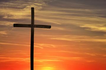 Christian cross over dark red sunset background