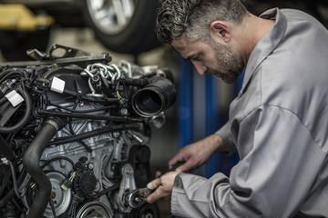 Car mechanic in a workshop repairing engine