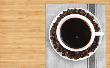top view dark coffee with beans in white cup on plate mat and wo