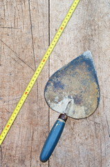 trowel and a tape measure on a wooden background