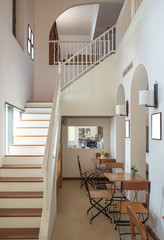 Interior vintage staircase with wooden tables and chairs