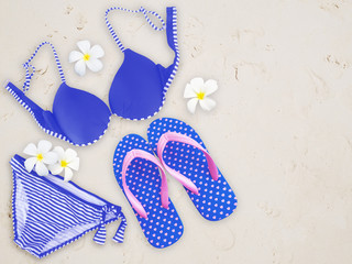 Fashionable woman swimming suit and flip flop on sand beach back