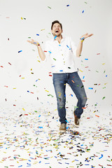 Man showered with confetti, studio shot