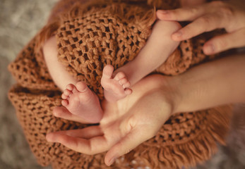 mothers hands holds cute and little legs of newborn baby