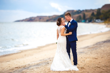 Young wedding couple enjoying romantic moments outside on the beach.