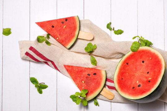Watermelon slices on sticks. Watermelon popsicle on wooden white