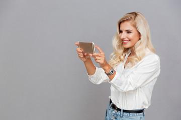 Beautiful young girl making photo on smartphone