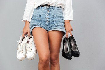 Young girl in denim shorts holding two pairs of shoes