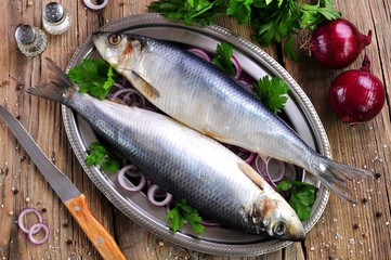 salted herring with red onion and parsley on the old wooden background.