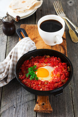 Shakshuka with tomato sauce and fried egg in a cast iron pan for breakfast on the old wooden background. Rustic Style, Selective Focus.