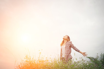 Young beautiful hipster woman in a flower field at sunset. Freed
