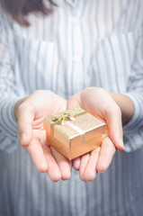Closeup, Woman hand holding gold gift box, female giving gift, New year holidays and greeting season concept, copy space.