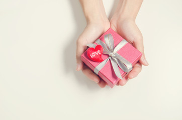 Closeup, Woman hand holding red gift box, female giving gift, New year holidays and greeting season concept, copy space. retro filter.