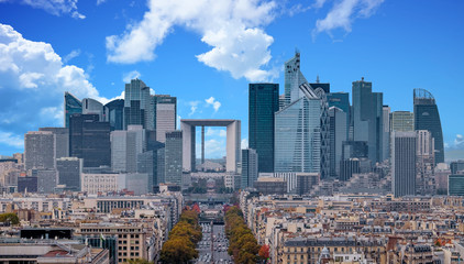 La Defense Financial District Paris France in autumn. Traffic on Champs-Elysees with orange and yellow trees aside. Modern vs. Old architecture. Blue sky with clouds.