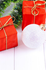 box with christmas gifts and decorations on a white wooden background