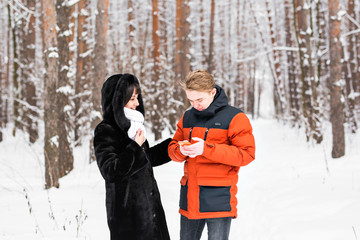 people, season, love, technology and leisure concept - happy couple with smartphone on over winter background