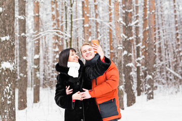 people, season, love, technology and leisure concept - happy couple taking picture with smartphone on over winter background