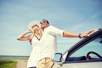 happy couple hugging near cabriolet car at sea
