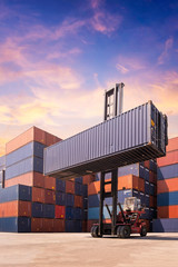 Forklift truck lifting cargo container in shipping yard or dock yard