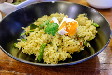 Rice yellow green curry with boiled egg in black dish