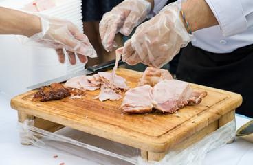 Chef sliced pork on wooden cutting board